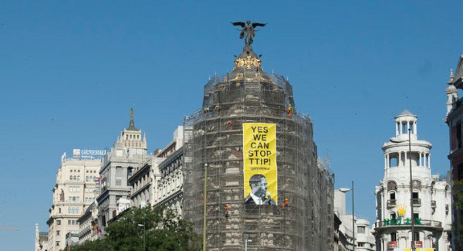 Activistas de Greenpeace cuelgan una pancarta en el edificio Metrópolis de Madrid para pedir a Obama que pare el TTIP