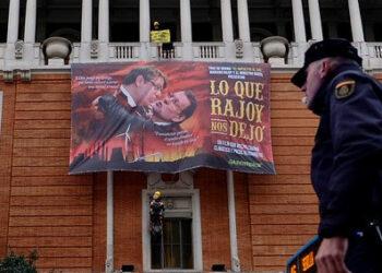 Greenpeace cuelga en la Gran Vía de Madrid un gran cartel de cine con Rajoy y el ministro Nadal de protagonistas para denunciar la política energética del Gobierno
