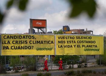 Activistas de Greenpeace cuelgan antes del debate de RTVE una pancarta para reclamar a los candidatos atención sobre la crisis climática