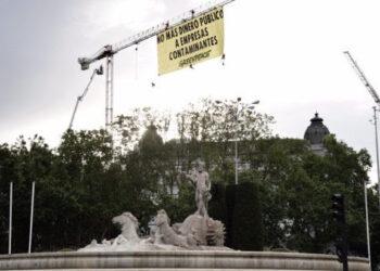 Escaladores de Greenpeace despliegan una pancarta junto al Congreso para exigir que no se destine más dinero público a empresas contaminantes